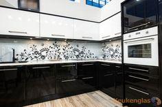 Witte glazen keukenwand met zwarte bloemversiering - Keukenglas