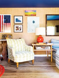 Beige wallpaper, surf wall art, American flag wall art, printed gold and white chair, wood coffee table, and red lamp