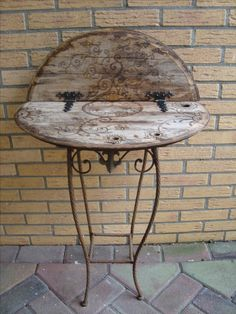 From an old lid of a wooden watertank and a little planttable I made a bigger sidetable. The lid was falling apart. I made a drawing on the lid with a wood burning tool. My husband screwed it to the top of the little planttable and made two iron supports at the back. I glued on some old hinges, which used to belong to my Father. I am quite pleased with the outcome.