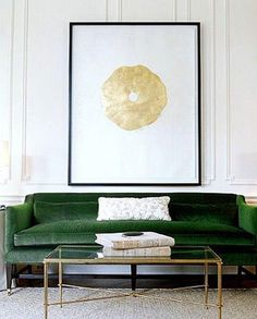 Gorgeous luxurious and traditional living room with minimalist styling in a bold color palette of black, white, gold and emerald green. Love the bronze and glass coffee table, oversized art print and velvet sofa.