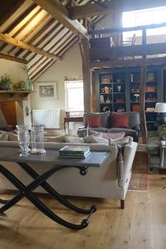Chiddingfold - drawing room in barn.  Bespoke shelving unit designed by Hudson Homes and painted in Paper and Paint Library Squid Ink.  All furniture to order