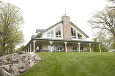 """The windows, wrap-around covered patio, the architectural features help this not scream """"Morton building"""" but home."""