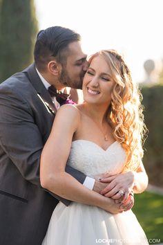 Groom cuddling his bride on their wedding day.