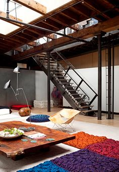 loft. floor seating. industrial staircase, colored pillows, low wooden table. Natural lighting