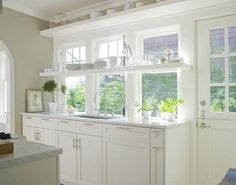 White Kitchen with open shelving in front of large windows - Mt. Baker home by Bosworth Hoedemaker via Houzz