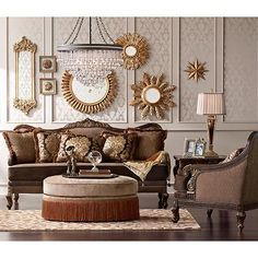 Varied shapes and sizes of gold medallion mirrors decorate an ornately wallpapered wall. Gold on cream.
