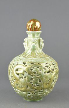 Chinese carved and glazed reticulated porcelain vase of celadon ground in bulbous form. Gilt gold dragons painted with a gold and red ball as the stopper. Four-character Kangxi mark on the base. H: 24 cm, D: 14 cm.