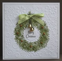 By lililindsay. Stamp wreath in center of cardstock. Dry emboss in snowflake folder. Stamp sentiment on scrap of white cardstock; circle punch. Add ribbon, gold pearls, and metal bells. Great card!