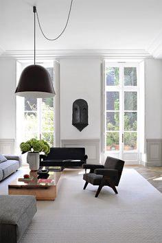 Joseph Dirand Paris luxe minimal living room white molding terrace doors Pierre Jeanneret chair copper table black bell pendant