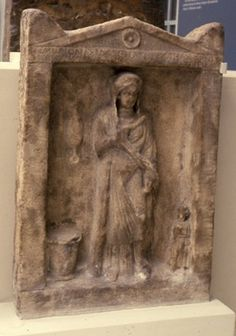 Marble funerary stele showing a woman with a girl attendant, and a distaff, spindle and wool basket; inscribed.
