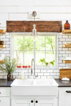 Every farmhouse needs a farmhouse sink. This Oklahoma home's kitchen features custom cabinetrytopped with quartz countertops and complementary subway tile with black grout.