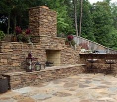 A fireplace constructed of El Dorado cultured stone veneer with natural Tennessee flagstone caps and hearth. Backyard Fireplace, Fireplace Wall, Fireplace Stone, Fireplace Ideas, Porches, Outdoor Stone Fireplaces, Backyard Retreat, Backyard Ideas, Big Backyard