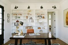 Chic home office features a dark stained desk paired with a cognac leather task chair atop a black and white print rug placed in front of black double doors.