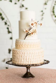 Brides.com: . Elegant rows of fondant leaves on the bottom tiers, combined with sugar dogwood flowers, give this pretty cake from Layers Cake an elegant-yet-organic look; the copper centers of the blossoms add just a hint of glam.   $5.50 per slice, Layers Cake