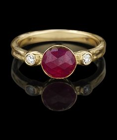 "INVINCIBLE THREE STONE  The ""Invincible"" ring is a classic 3-stone ring as seen through Karen Karch's eyes. Shown in hand-textured 18k yellow gold with a round 1.14 ct rose-cut bright red natural ruby, and round brilliant colorless diamond side stones, 0.08 ct total.  $5,500"