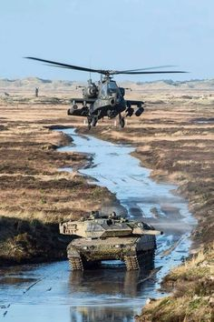 Army helicopter crew, assigned to Combat Aviation Brigade, provides over watch for a Danish Leopard 2 battle tank moving into initial battle position on the live-fire range during Operation White Sword at the Oksbol Training Area, Denmark, Dec. Attack Helicopter, Military Helicopter, Military Aircraft, Army Vehicles, Armored Vehicles, Photo Avion, Ah 64 Apache, Battle Tank, Military Weapons