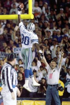 Cowboys wide receiver Alvin Harper spikes the ball through the goal post after…