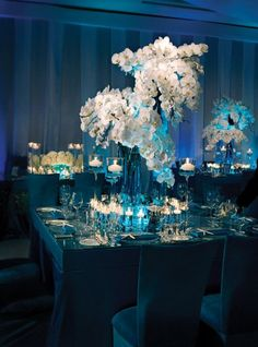 Aquamarine taffeta shadowbox tables featuring LED lighting, crushed blue glass, seashells, mercury balls and white phalaenopsis orchids