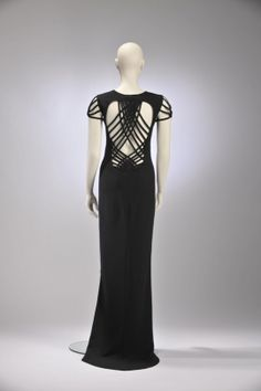 Designer: Jean Paul Gaultier Brand: Jean Paul Gaultier Label: Jean Paul Gaultier FEMME Material: 64% tri-acetate 36% polyester 1999-2000 This full-length black evening dress is open at the back with strap lacing that forms a webbed design. The same web-like structure also creates the impression of cap sleeves. Strong lines on bare skin are an element frequently seen in Gaultier's designs.MODEMUSEUM HASSELT
