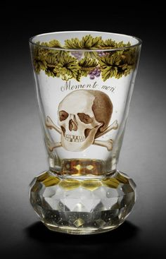 A Bohemian transparent enamelled 'Memento Mori' beaker by August Mohn, dated 1817 The flared bowl painted with a skull and crossed bones inscribed Memento mori below a band of fruiting vine, the facet-cut solid base part stained in amber, 11cm high, inscribed A Mohn pin. 1817