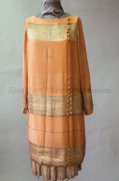 C. 1926, Salmon silk woven with silver lame afternoon dress. Dress with high neck and long sleeves, bands of lame at neck, hip, cuff and hem all with rows of buttons, underskirt of pleated lame.