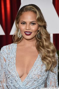 Chrissy Teigen channels Queen Bey here with those retro-inspired waves, bronzed skin and creamy wine lipstick.