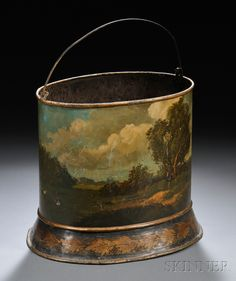 Toleware Wastebasket, England, 19th century, oval shape with a bail handle, painted with a panoramic landscape scene with a house, river, and figures, raised on a slightly flared foot painted with a band of gold leaves against a black background, ht. 11 3/8, lg. 12 1/2, dp. 9 1/2 in.
