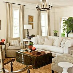 Large coffee table, chair placement, drapes Drapes and pillows, rug