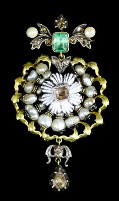 A 19th Century Austro-Hungarian gold coloured metal enamel pearl and gem set boss pattern pendant, the central white enamelled flower within pearl border to scrolling gold coloured metal edge, 68mm x 35mm overall, (gross weight 11.4 grammes)