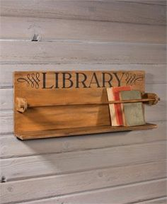 """Love the look of old schoolhouse decor? This book display shelf is perfect for you. The Vintage Style Schoolhouse Bookshelf with Dowel Rod is a great way to keep books front and center in your farmhouse. This reproduction of a classic schoolroom find features a dowel rod and the word """"Library"""" prominently displayed. Create a vintage style reading nook with this old-school bookshelf."""