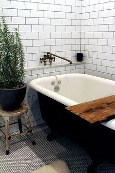 love love love the clawfoot tub with the reclaimed wood beam and rusted stool... and the plant.... and the bath tap! not so much the walls or floors, but hey, can't win em all