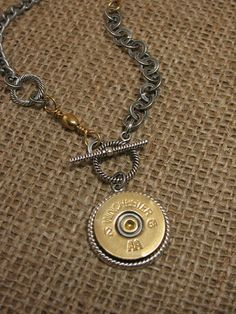 Shotgun casing and bullet casing jewelry and accessories from Key of As SureShot™ Collection  One of our best selling necklaces to date from the SureShot™ collection. Popular toggle medallion necklace featuring a brass 12 gauge shotgun casing mounted in our signature rope bezel. The shell has a brass/silver primer that sets the stage for the mixed metal look of the entire design.  Mixed chain styles in an asymmetrical pattern combined with rope rings and genuine barrel fishing swivels give…
