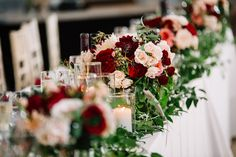 {{Head table at a late summer wedding with coral garden roses, blush spray roses, cream and red dahlias, garland, and candles at head table at Galleria Marchetti in Chicago.}} Photography by Laura Fisher Photography http://www.laura-fisher-photography.com/ || Flowers by Pollen, pollenfloraldesign.com