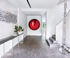 A deep red Anish Kapoor sculpture greets visitors in the entrance hall of a midcentury house in the suburbs of Paris, designed by Charles Zana for a couple with a blue-chip contemporary art collection. The text painting is by Richard Prince, and the console is by Eric Schmitt; a dramatic glass-bead sculpture by Jean-Michel Othoniel dangles from 30 feet above.