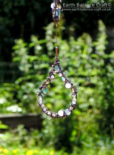 Rain Drops Sun Catcher – A patina copper free-form wire hanging ornament with three rain drop shapes wire wrapped with agate, kyanite, labradorite, glass, opalite, fluorite and crystal chip beads.  This pretty hanging decoration is suitable for both the home and garden.  The design was inspired by summer rain with translucent watery green and blue flashes of rainbow colours.  A hand crafted piece made by Nicola Jones in her Horsham studio, West Sussex.