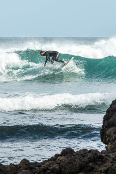 Catching a wave at Piha Beach on the west coast of Auckland New Zealand.  The article contains images of black sand beaches, waterfalls, rainforest, and surfers.