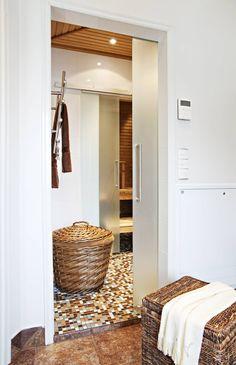 Liukuoven takana olevaa saunaosastoa käytetään usein. Pyyheliinat kuivuvat Rej-Designin rättipatterilla ja ruskeaan, isoon koriin mahtuu likapyykki.