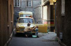 Junge Frau und Kind putzen in der Altstadt von Erfurt einen gelben Pkw Trabant, zwischen 1980 und 1983. © Archiv Bundesstiftung Aufarbeitung, Fotobestand Uwe Gerig