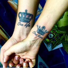 "A gorgeous pair of king and queen couple tattoos with the often used ""One life, One love,"" lettering."