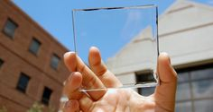 Researcher Yimu Zhao holding up a transparent luminescent solar concentrator module - Photography: Yimu Zhao