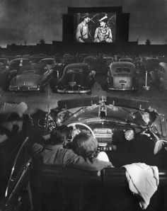 Young couple snuggling behind the wheel of his convertible as they watch large screen action behind rows of cars at a drive-in movie theater in Los Angeles, CA. Photograph taken by J. R. Eyerman, 1949.