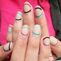 Not quite French tips, not quite half-moons: Thin, colorful arches lengthen and add interest to nude nails.