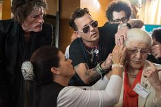Johnny Depp Photos - Joe Perry and Johnny Depp help a patient of the Starkey Hearing Foundation at Four Season Hotel Ritz Lisbon on May 27, 2016 in Lisbon, Portugal. - Starkey Hearing Foundation Hearing Mission With Hollywood Vampires - Rock in Rio Lisboa 2016