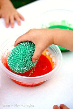 Painting with kitchen scrubbers for added sensory play.