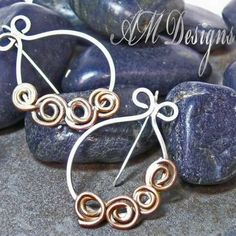 "Handcrafted Artisan Sterling Silver Copper Spirals Wire Hoop Earrings    The copper spiral swirls on these hand forged sterling silver hoops are like new life unfurling, like the fronds of a new fern opening to the sun. The versatility of mixed metals make these stylish earrings a necessary addition to your accessory collection. Earring measure approximately 1.5"" (3.8cm)    Artfully Handcrafted Jewelry by AMDesignsbyAngela"
