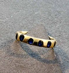 Polly+Wales+Slim+Crystal+Blue+Sapphire+Ring+-+Polly's+innovative+process+involves+an+array+of+gemstones+placed+in+precious+metals+that+create+a+slightly+unpredictable+outcome+with+a+rough+luxe.Metal:+18K+goldStones:+Blue+sapphires+Band:+4mmSize:+6+1/2