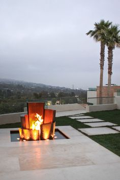 Five curved copper structures of varying height and width surround a large flame located in the center of a shallow reflecting pool clad in granite. The outer surfaces of the curved structures are ridged to create cascading waves of water. Underwater lights and dancing fire on water illuminate the sculpture at night.