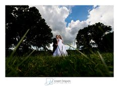 Dramatic wedding portrait in the park, featuring plenty of blue skies and white puffy clouds.  This was taken using a strong off camera light source for some dramatic lighting.  #njweddingphotographer #weddings #epicweddingphotos