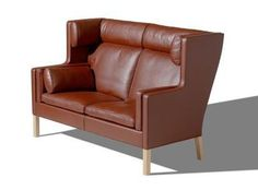 An elegant high-backed leather sofa designed in 1971. Mogensen wanted to design a sofa for peaceful relaxation in front of the fireplace. He was inspired by the distinctive lines of the British hall porters chair - a classic wing-style chair specially designed to capture heat from the open fireplaces typical of the cold housing of the past. In Danish, the popular term for this model is a compartment sofa because it fits snugly round its occupant like the comfortable seats in a first-class t