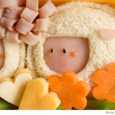Here's how to make an easy sheep bento lunch box using sandwiches, a ham flower and veggie shapes